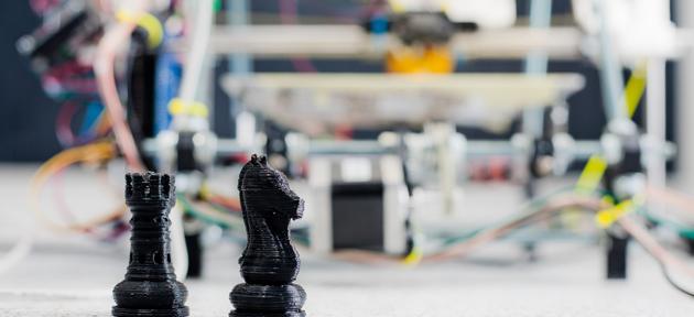Na imagem vemos peças de xadrez e objetos de robótica ao fundo
