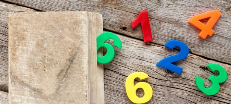 Números coloridos saindo de um pacote e espalhados sobre um chão de madeira